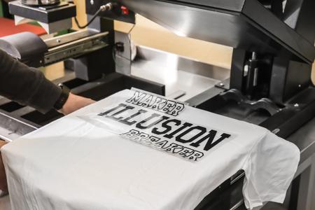 Photo pour Young man printing on t-shirt at workshop - image libre de droit