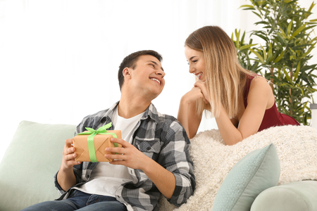 Foto per Young woman giving present to her beloved boyfriend at home - Immagine Royalty Free