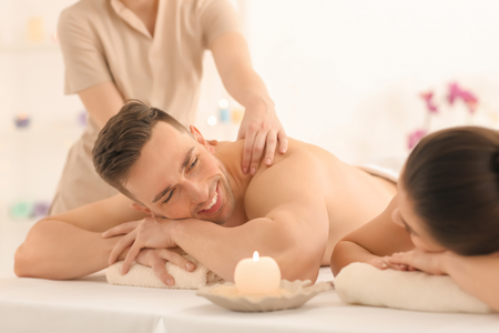 Foto de Happy young couple having massage in spa salon - Imagen libre de derechos