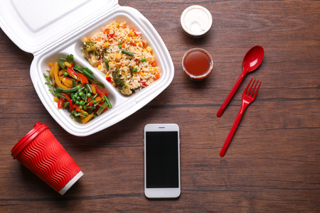 Photo pour Flat lay composition with smartphone and takeout meal on wooden background. Food delivery - image libre de droit