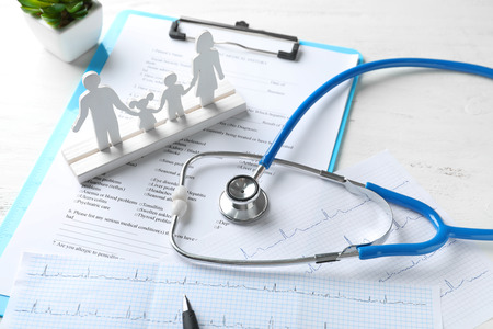 Foto de Composition with family figure and stethoscope on wooden table. Health care concept - Imagen libre de derechos