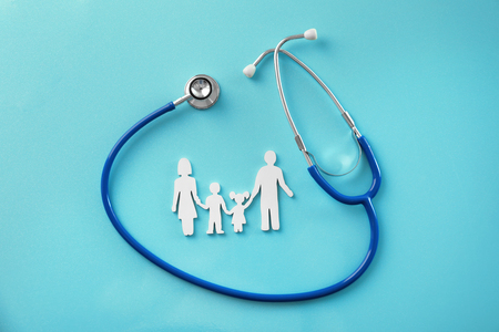 Foto de Family figure and stethoscope on color background. Health care concept - Imagen libre de derechos