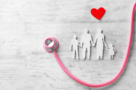 Foto de Family figure, red heart and stethoscope on wooden background. Health care concept - Imagen libre de derechos