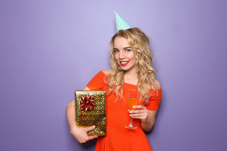 Photo for Portrait of beautiful young woman with birthday gift and glass of champagne on color background - Royalty Free Image