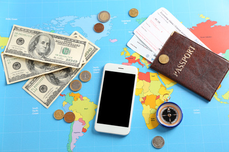 Photo pour Mobile phone, passport and money on world map. Travel concept - image libre de droit