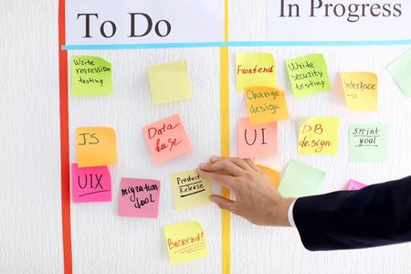 Foto de Man attaching sticky note to scrum task board in office - Imagen libre de derechos