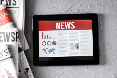 Photo pour Tablet computer with news on screen on textured background - image libre de droit