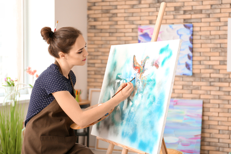 Photo for Female artist painting picture in workshop - Royalty Free Image