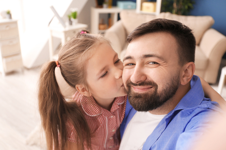 Photo pour Emotional father and daughter taking selfie at home - image libre de droit