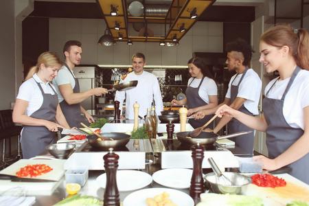 Foto de Chef and group of young people during cooking classes - Imagen libre de derechos