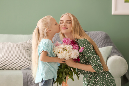 Photo pour Attractive young woman and her cute little daughter with beautiful flowers at home - image libre de droit