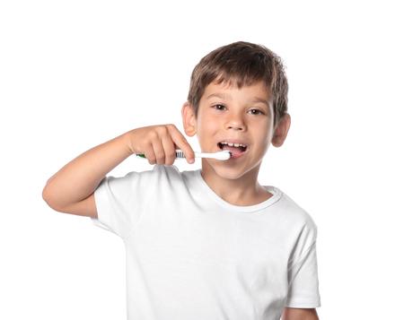 Photo pour Cute little boy brushing teeth on white background - image libre de droit