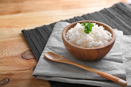 Foto per Bowl with boiled white rice on wooden table - Immagine Royalty Free