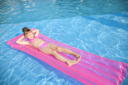 Photo pour Cute little girl resting on inflatable mattress in swimming pool - image libre de droit