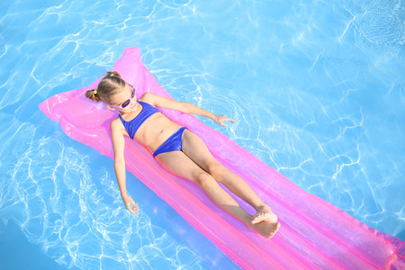Foto de Cute little girl resting on inflatable mattress in swimming pool - Imagen libre de derechos