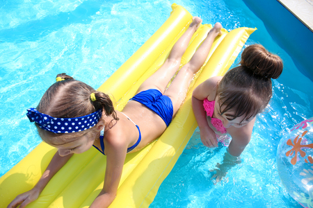 Photo pour Cute children playing in swimming pool on summer day - image libre de droit