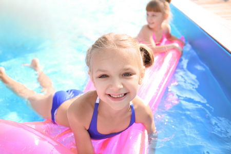 Photo pour Cute children swimming in pool on summer day - image libre de droit