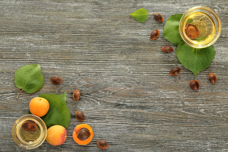 Photo for Bowls with essential oil and fresh apricots on wooden table - Royalty Free Image