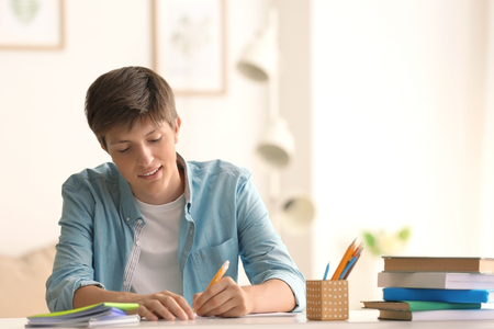 Photo pour Teenager boy doing homework at home - image libre de droit