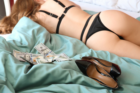 Foto de Young prostitute in lingerie and with money lying on bed - Imagen libre de derechos