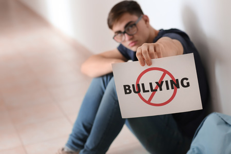 Photo pour Teenage boy holding sheet of paper with word BULLYING while sitting on floor at school - image libre de droit