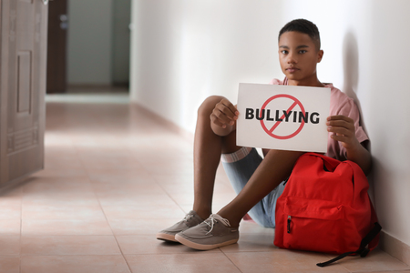 Photo pour African-American teenage boy holding sheet of paper with word BULLYING while sitting on floor at school - image libre de droit