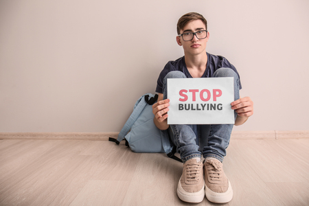 Photo pour Teenage boy holding sheet of paper with text STOP BULLYING while sitting on floor indoors - image libre de droit