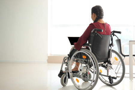 Photo pour Asian woman in wheelchair working with laptop in office - image libre de droit