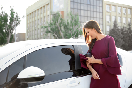 Photo pour Young businesswoman with caught dress in car door because of hurrying - image libre de droit