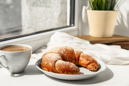 Foto de Plate with tasty fresh crescent roll and cup of cocoa drink on windowsill - Imagen libre de derechos