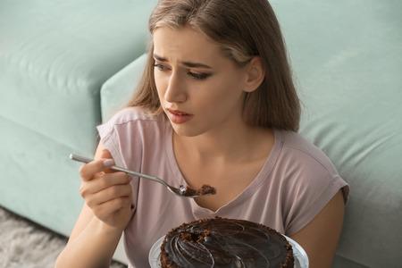 Foto de Lonely depressed woman eating chocolate cake at home - Imagen libre de derechos