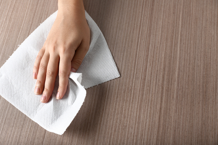 Photo for Woman wiping wooden table with paper towel - Royalty Free Image
