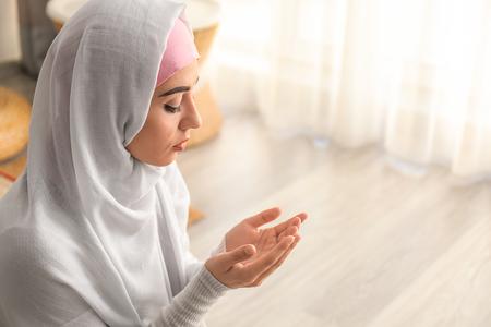 Photo pour Young Muslim woman praying at home - image libre de droit