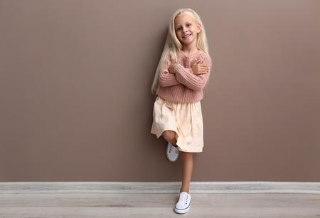 Photo pour Cute girl in fashionable clothes near color wall - image libre de droit