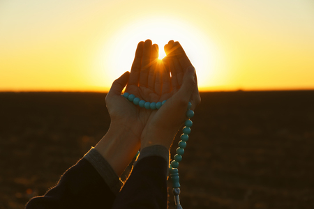 Photo pour Young Muslim woman praying with beads outdoors at sunrise - image libre de droit