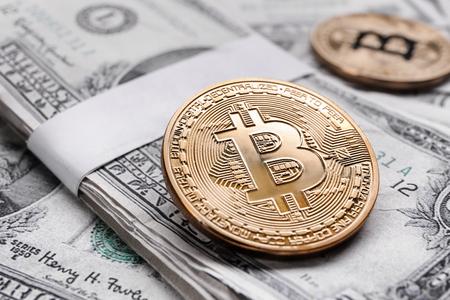 Photo pour Golden bitcoins on dollar banknotes - image libre de droit