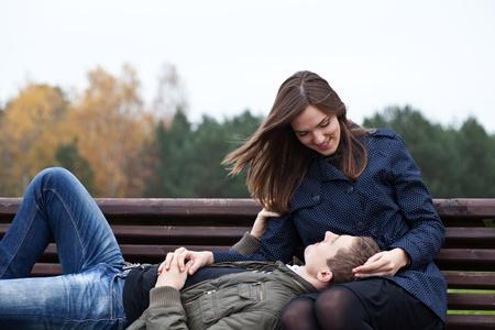 Foto für man lying in lap of young woman on park bench - Lizenzfreies Bild