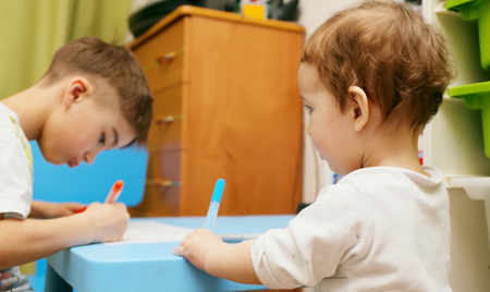younger brother is watching and copying actions elder brother (drawing in the nursery)