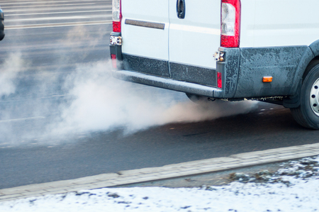Foto de Pollution of the atmosphere by gas from the exhaust pipe of a white van in motion in the city. Combustion fumes coming out of back car in winter time. Air pollution concept. Motion blur. - Imagen libre de derechos