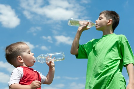 Two boys are drinking whater outdoors against the sky