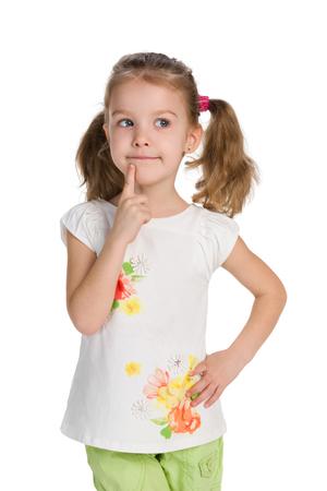 Foto de A curious little girl stands against the white background and thinks - Imagen libre de derechos
