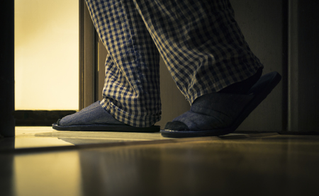 Photo pour Adult man in pijamas walks to a bathroom at the night. Mens healths concept - image libre de droit