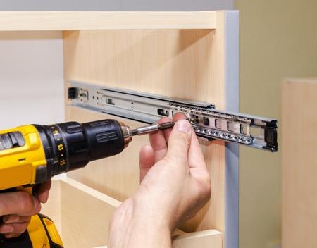 Photo pour Assembling furniture from chipboard, using a cordless screwdriver, close up. - image libre de droit