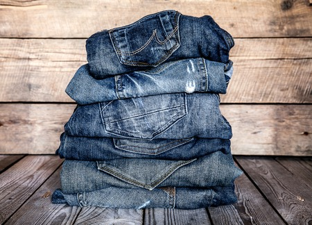 Photo for fashionable clothes. pile of jeans on a wooden background - Royalty Free Image