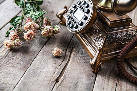 Photo for Old vintage black rotary phone and a bouquet of roses on wooden background - Royalty Free Image