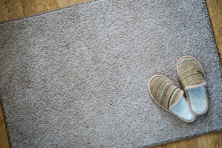 Photo for Slippers on the mat, top view with space for text - Royalty Free Image