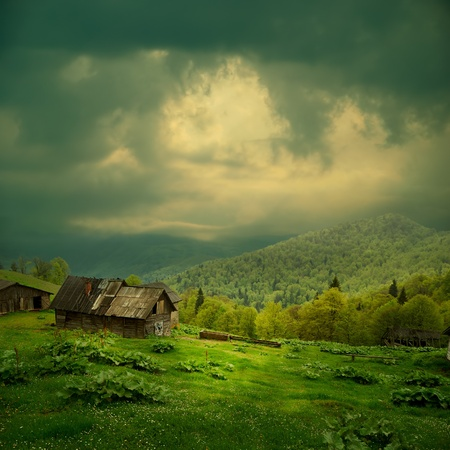 Photo pour Mystery mountain landscape. Ray of light in dark clouds over the old wooden shack in green valley - image libre de droit