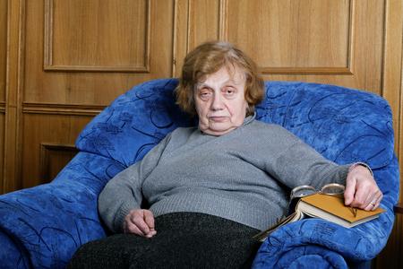 Foto de The old woman sits in an armchair and reads the book - Imagen libre de derechos