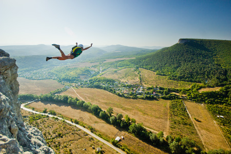 Foto de base-jumper jumps from the cliff at sunrise in the mountains - Imagen libre de derechos