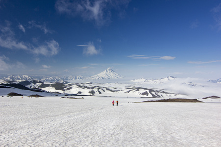 Photo pour two men on snowy field in kamchatka mountains near covered by snow volcanoes - image libre de droit